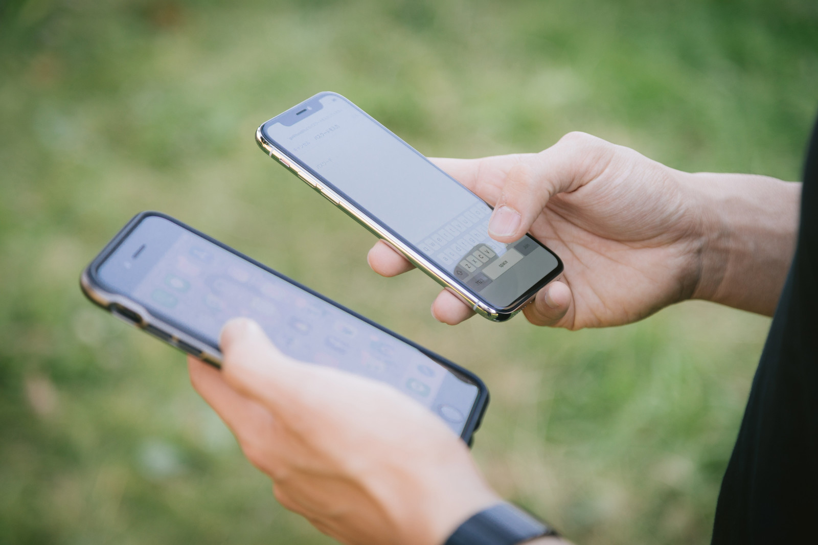 「2台のスマホ(iPhone)を操作する男性の手」の写真