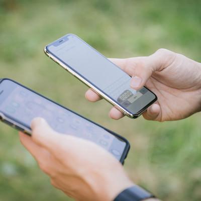 「2台のスマホ(iPhone)を操作する男性の手」の写真素材