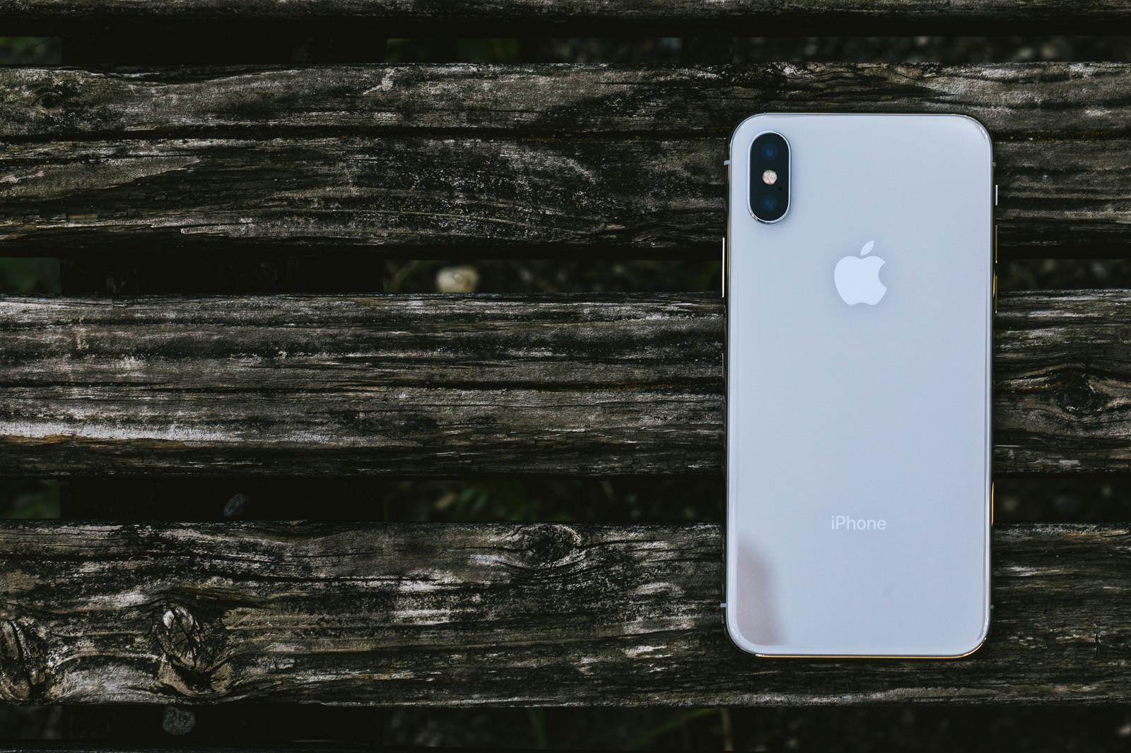 「木の板と iPhone X (背面)」の写真