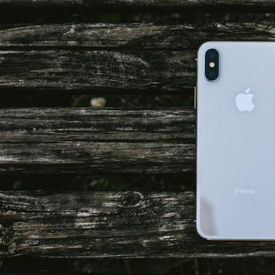 木の板と iPhone X (背面)の写真