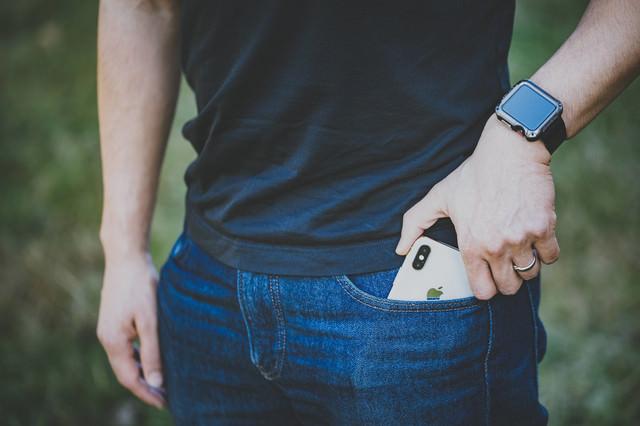 iPhone X をジーンズのポケットから取り出すシーンの写真