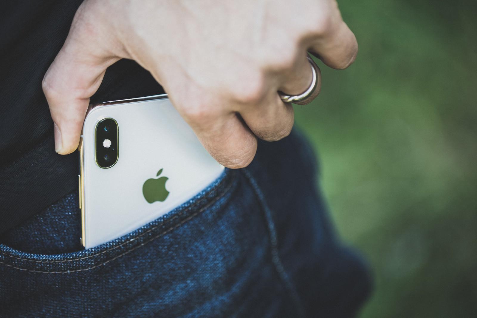 「ポケットから iPhone X を取り出す男性の手」の写真