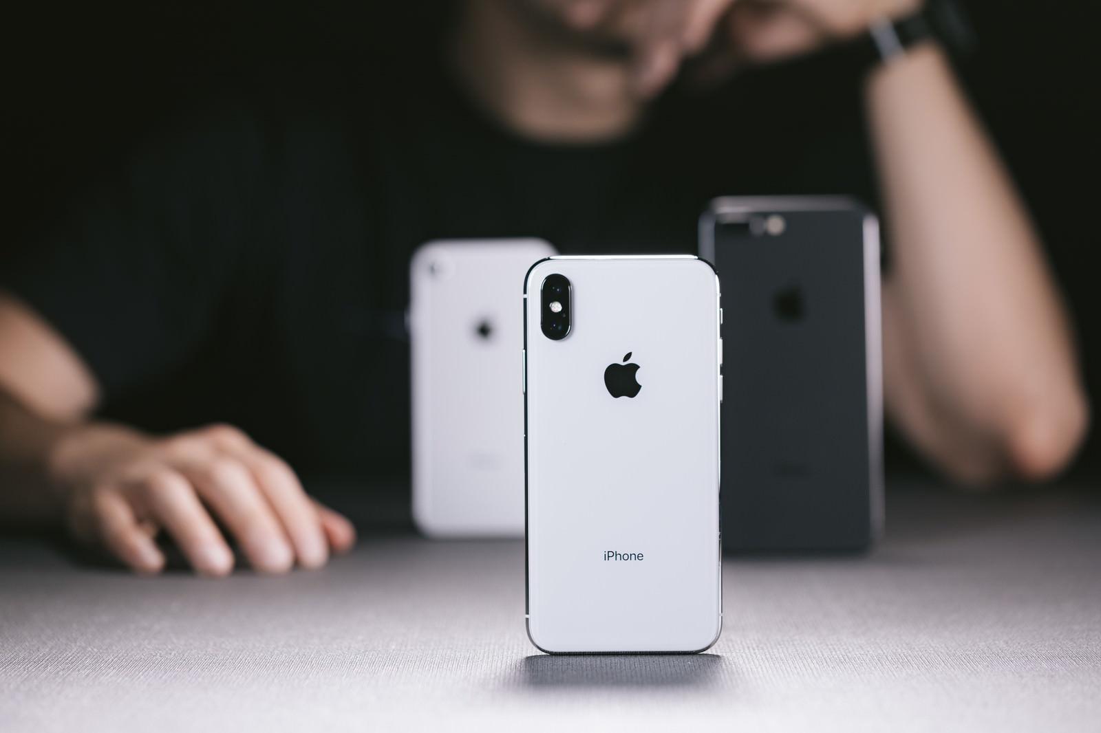 「iPhone X と iPhone 8 を並べて考える男性」の写真