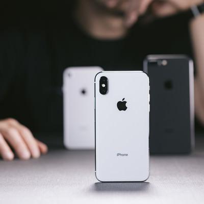 「iPhone X と iPhone 8 を並べて考える男性」の写真素材