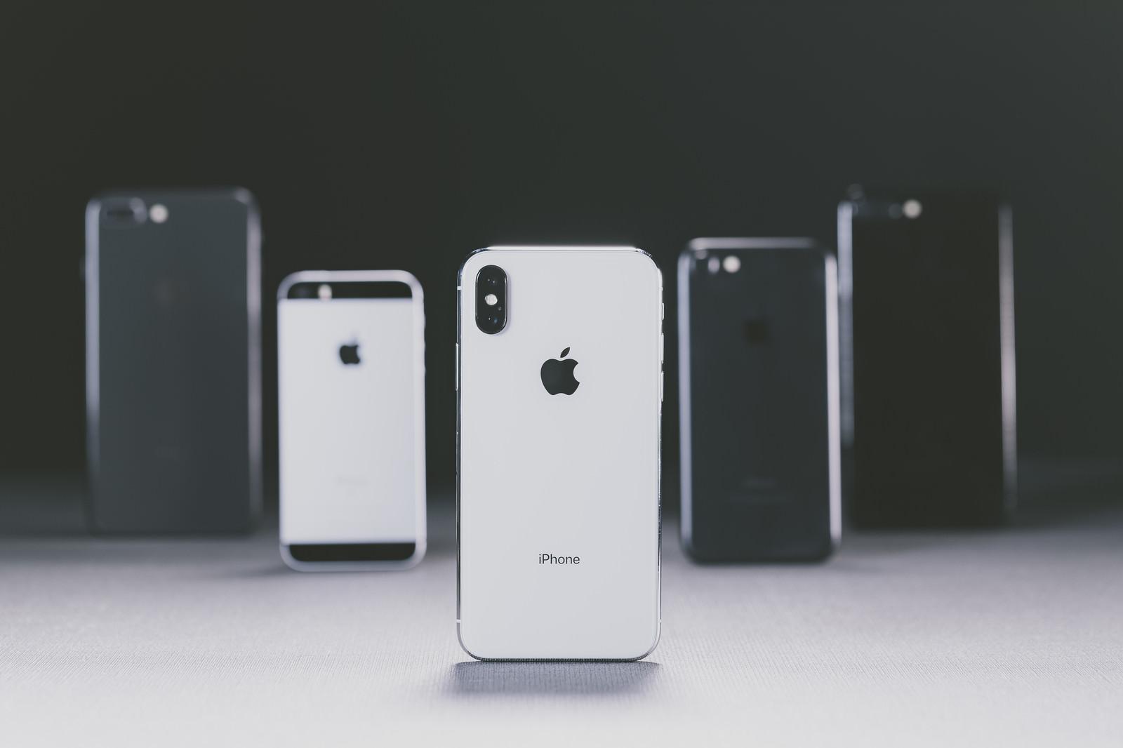「iPhone X と並べられた別モデルの iPhone」の写真