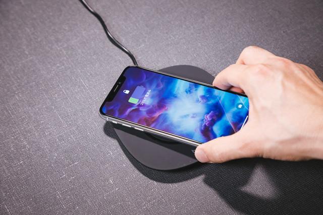 ワイヤレス充電器にスマートフォン(iPhone X)をかざすの写真