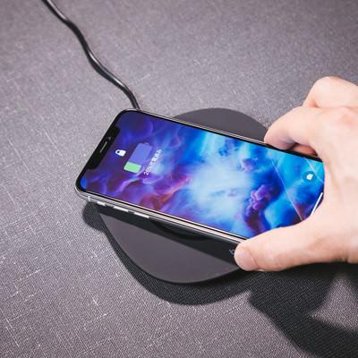 「ワイヤレス充電器にスマートフォン(iPhone X)をかざす」の写真素材
