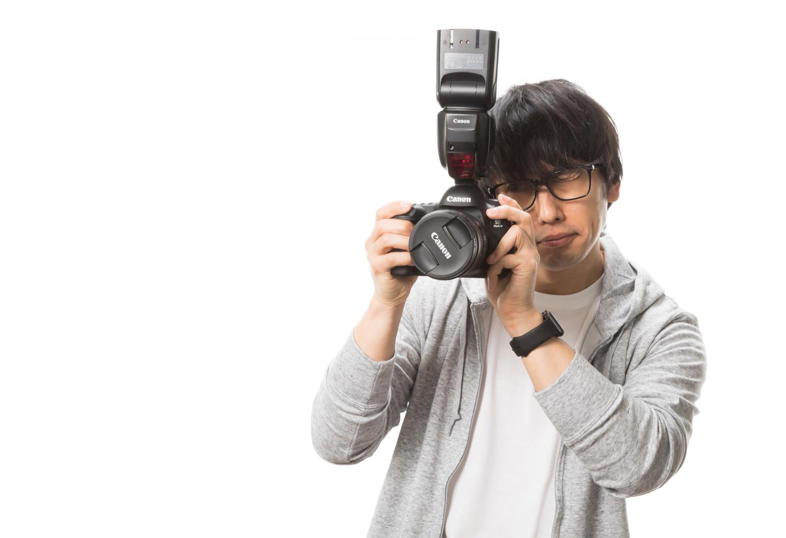 「レンズキャップの外し忘れに気づかない初心者フォトグラファー」の写真[モデル:大川竜弥]