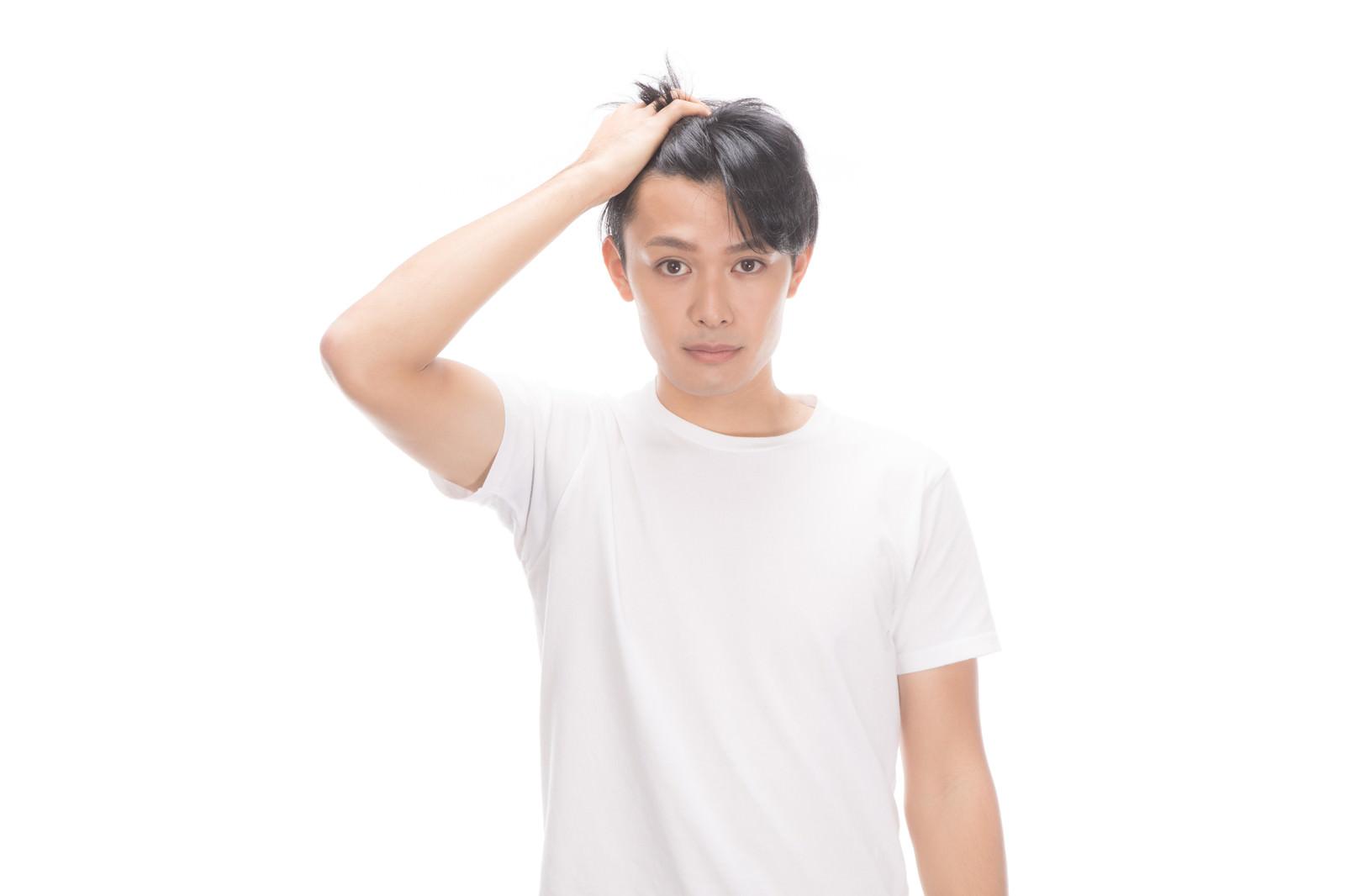 「前髪をあげておでこの広さを見せる若い男性」の写真[モデル:完伍]