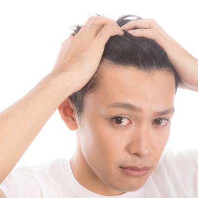 「髪をかきあげておでこを見せる男性」の写真素材