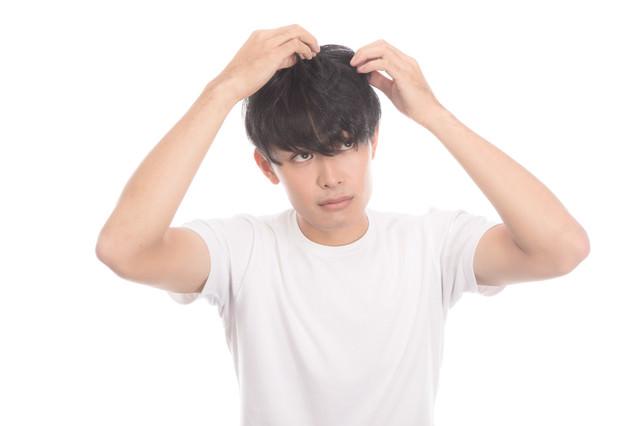 頭髪を気にする若い男性の写真