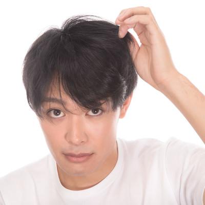 「髪の毛の量を気にする若い男性」の写真素材