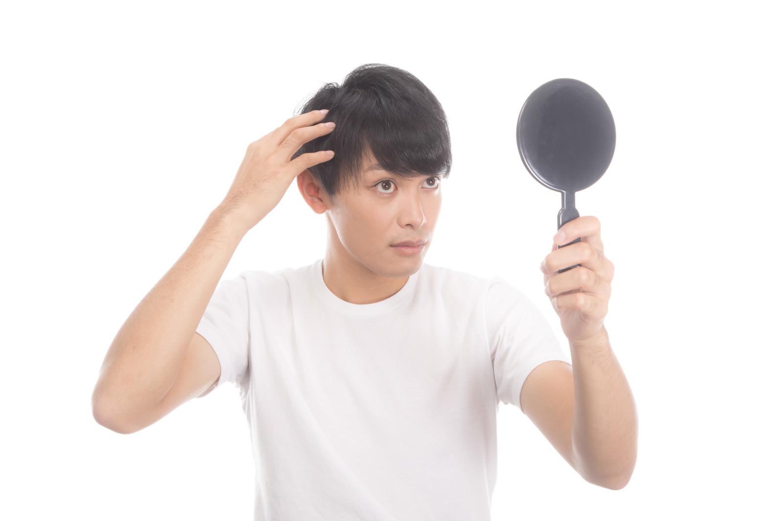 「手鏡で薄毛・生え際のヘアチェックをする若い男性」の写真[モデル:完伍]