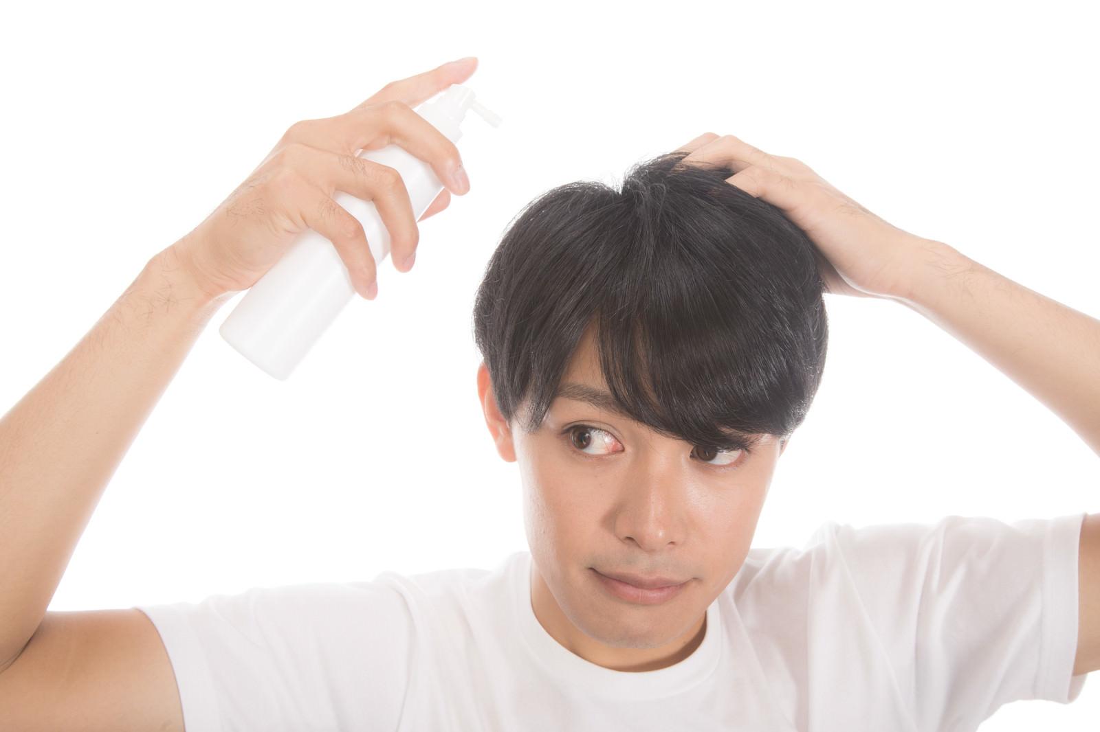 「増毛スプレーを使う若い男性」の写真[モデル:完伍]