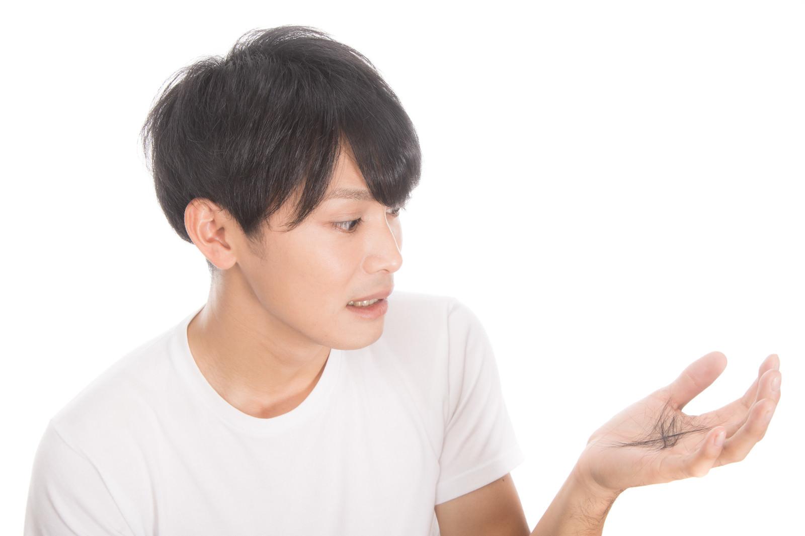 「抜け毛を気にする若い男性」の写真[モデル:完伍]