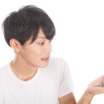 「抜け毛を気にする若い男性」の写真素材