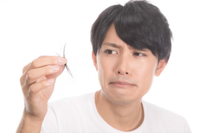 頭髪の抜け毛が気になりはじめる若い男性の写真