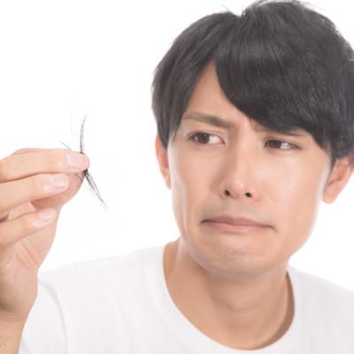 「頭髪の抜け毛が気になりはじめる若い男性」の写真素材