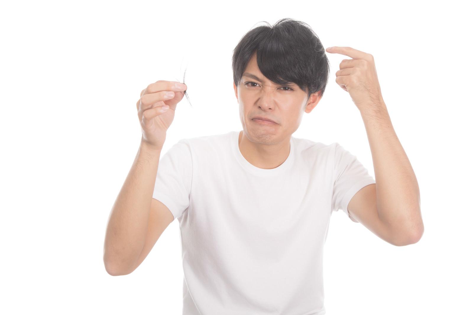 「髪の抜け毛を気にする若い男性」の写真[モデル:完伍]