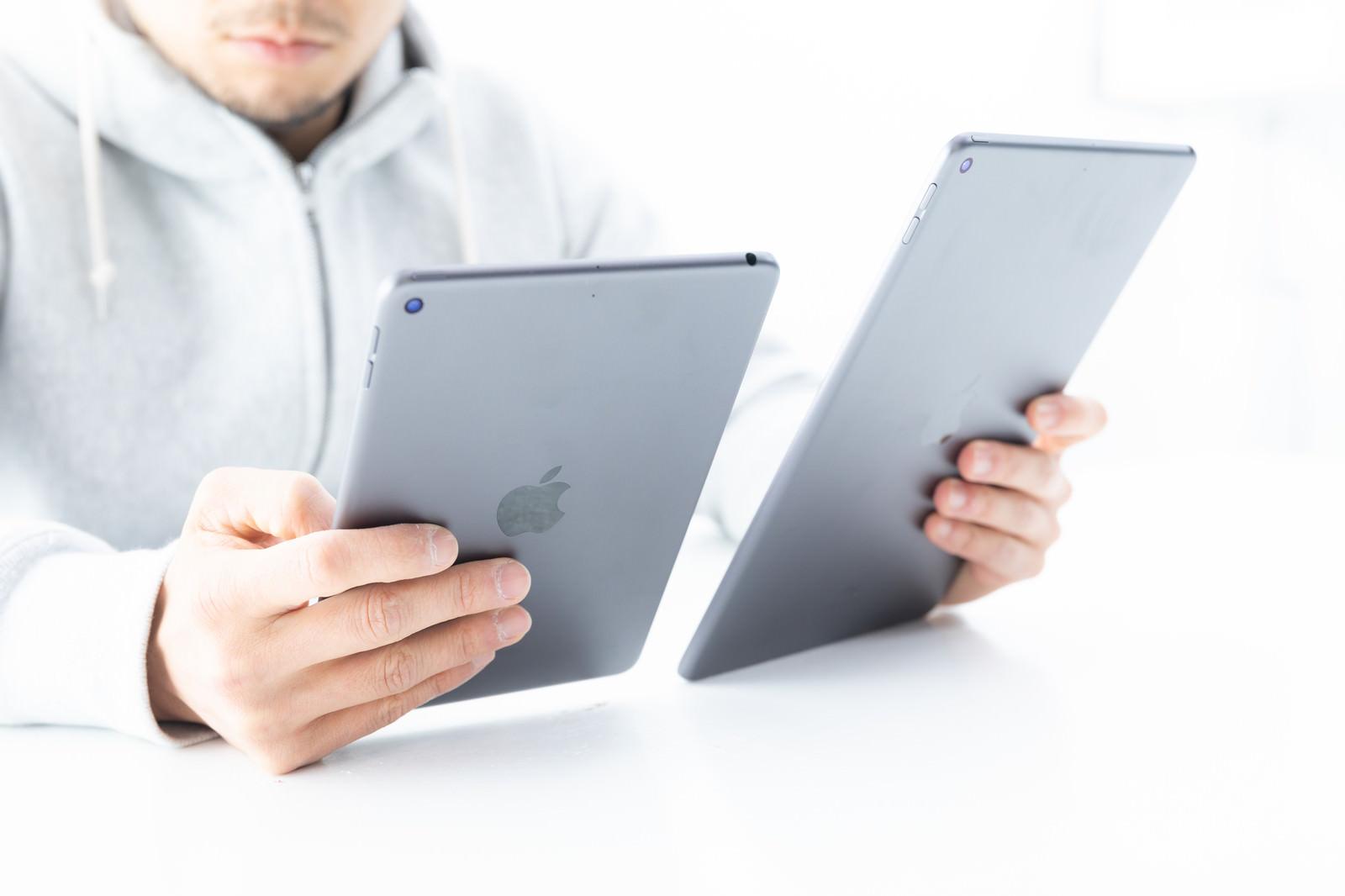 「iPadのディスプレイを細かく見比べる男性」の写真