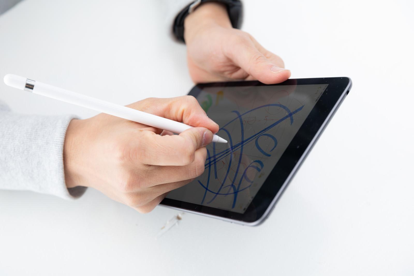 「Applepencilの書き心地を確かめる男性」の写真