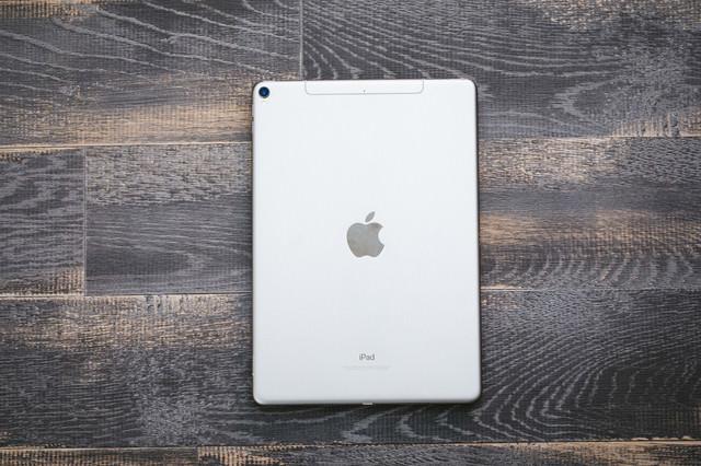 木目のテーブルに置かれたタブレット(iPad)の写真