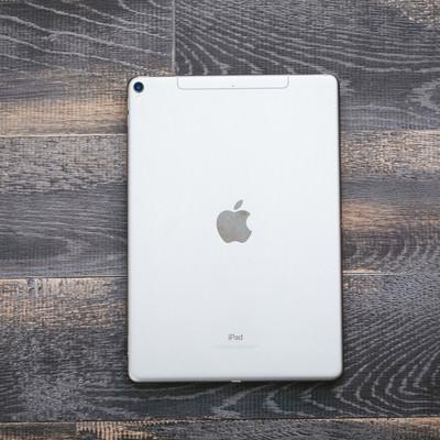 「木目のテーブルに置かれたタブレット(iPad)」の写真素材