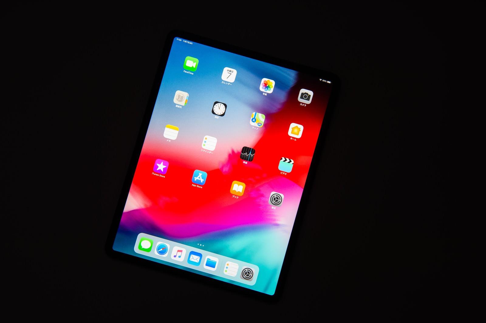 「黒い背景に傾けたタブレットのホーム画面(12.9インチ iPad Pro 2018)」の写真