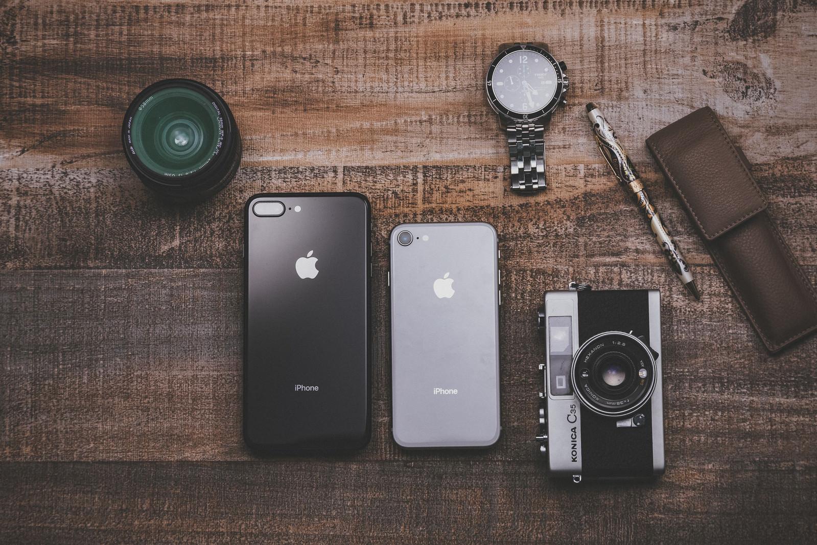 「木目のテーブルに置かれた最新スマホとカメラやレンズの所持品」の写真
