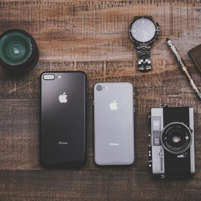 「木目のテーブルに置かれた最新スマホとカメラやレンズの所持品」の写真素材