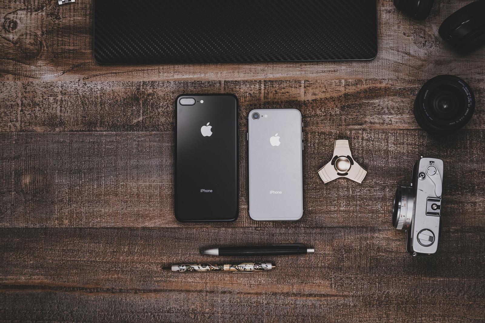 「木目調のテーブルに置かれたiPhoneなど」の写真[モデル:iPhone]