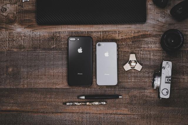 「木目調のテーブルに置かれたiPhoneなど」のフリー写真素材