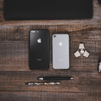 木目調のテーブルに置かれたiPhoneなどの写真