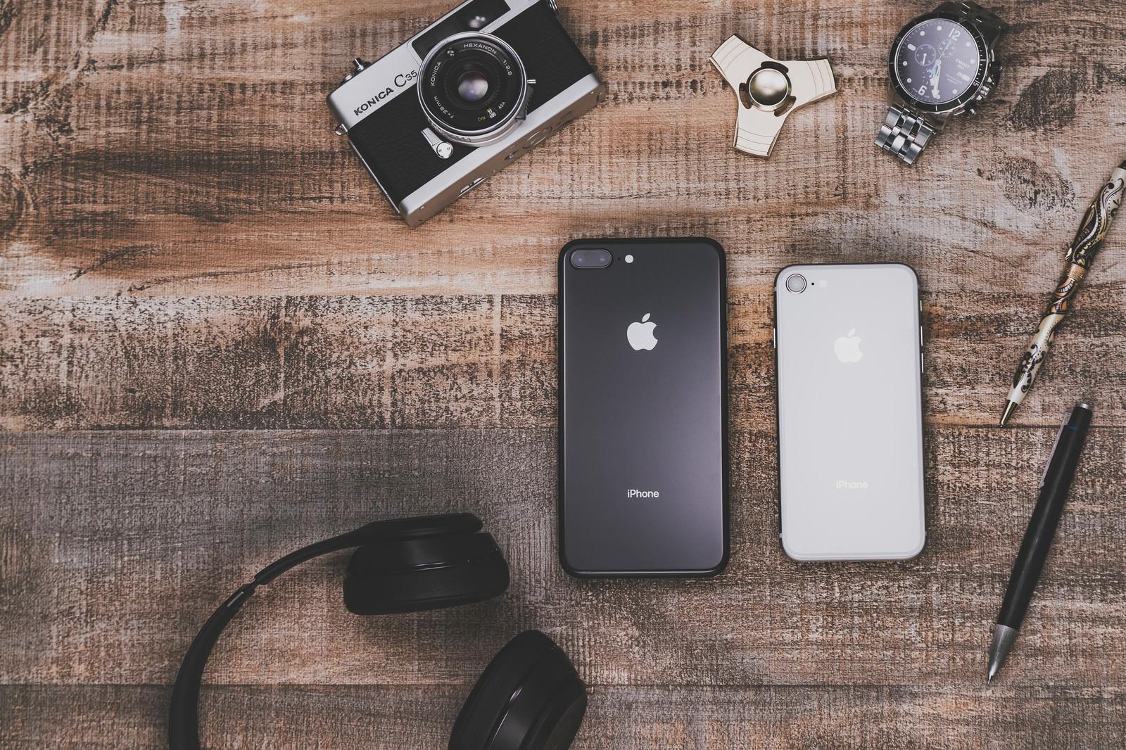 「テーブルの上に散らばったiPhoneや小物」の写真