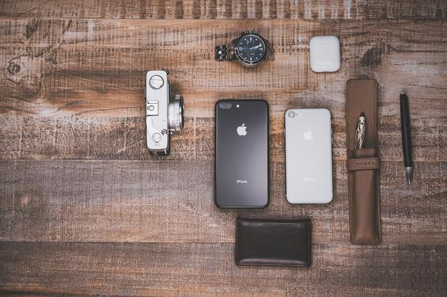 木目のテーブルに置かれたiPhoneや小物の写真