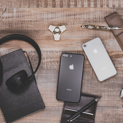 「デスクの上に置かれたiPhoneや小物」の写真素材