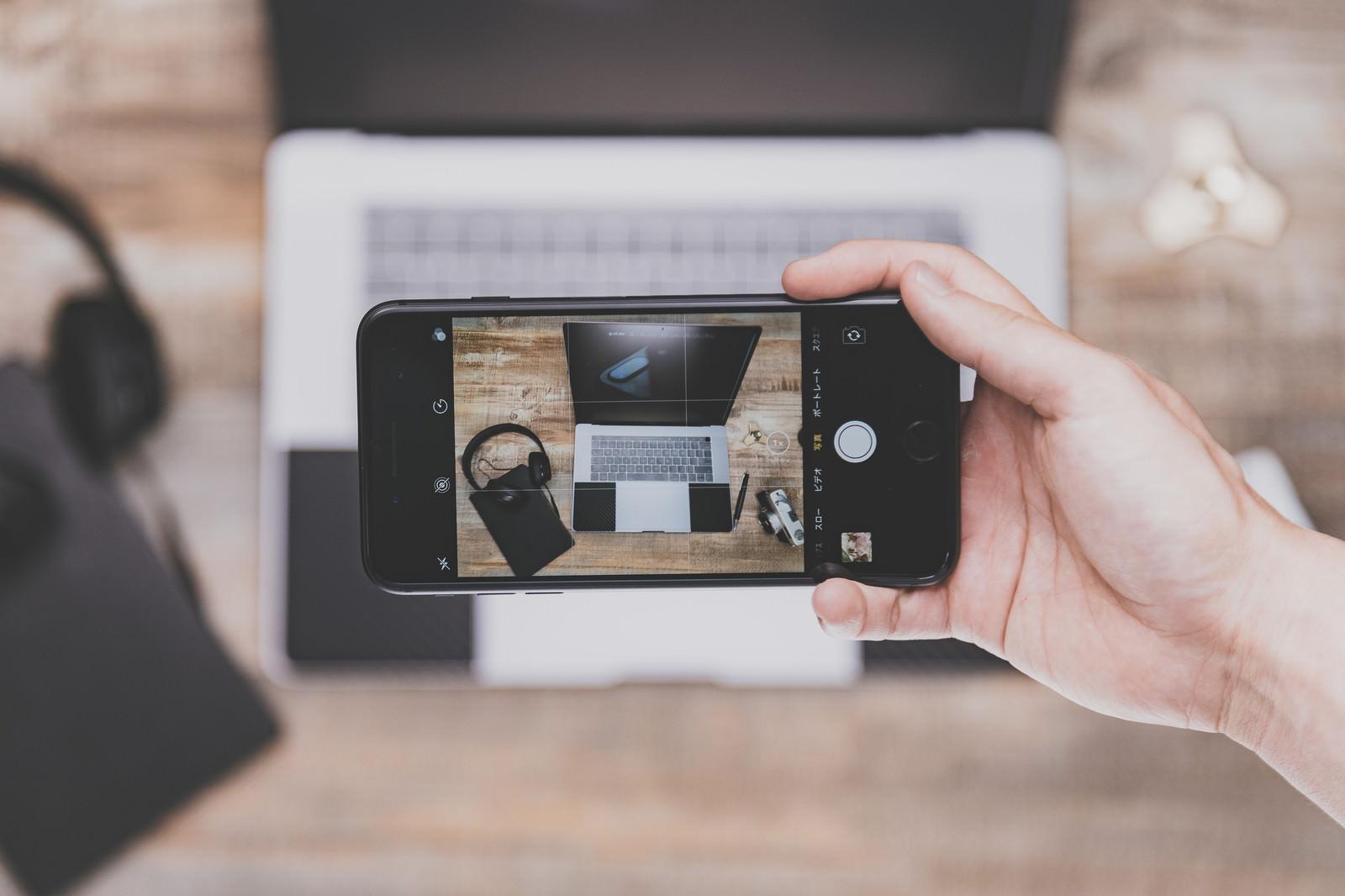 「テーブルに置かれたノートPCをiPhoneで撮影」の写真