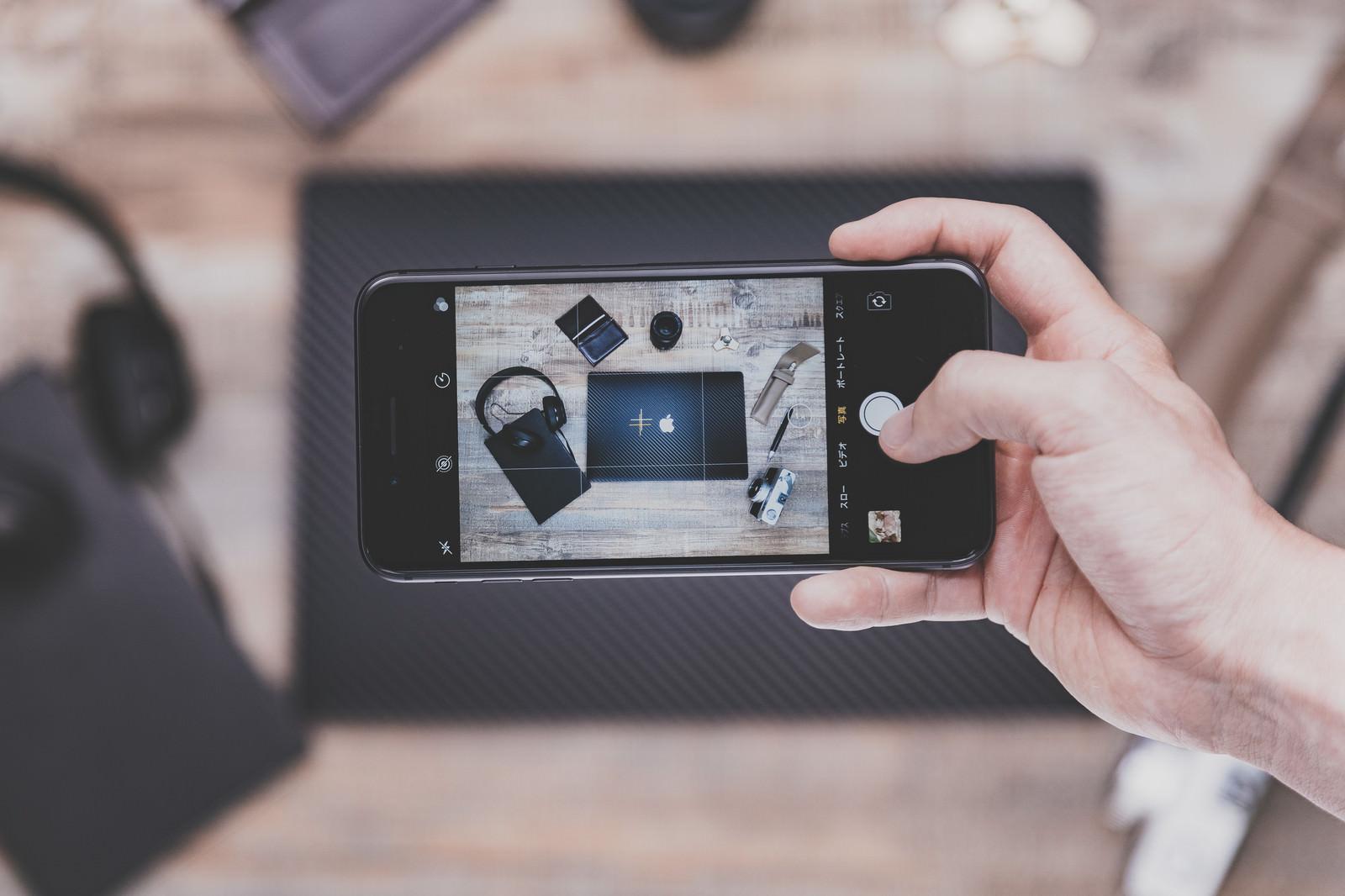 「テーブルに置かれたガジェットをiPhoneで撮影(横位置)」の写真