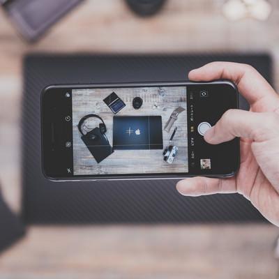 「テーブルに置かれたガジェットをiPhoneで撮影(横位置)」の写真素材