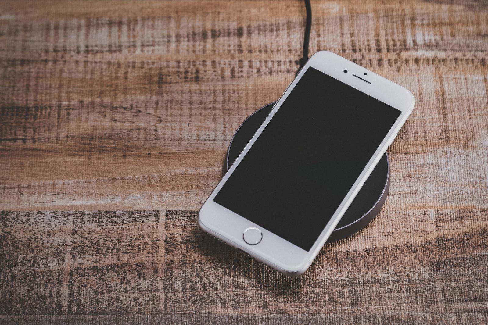 「ワイヤレス充電中のiPhone」の写真