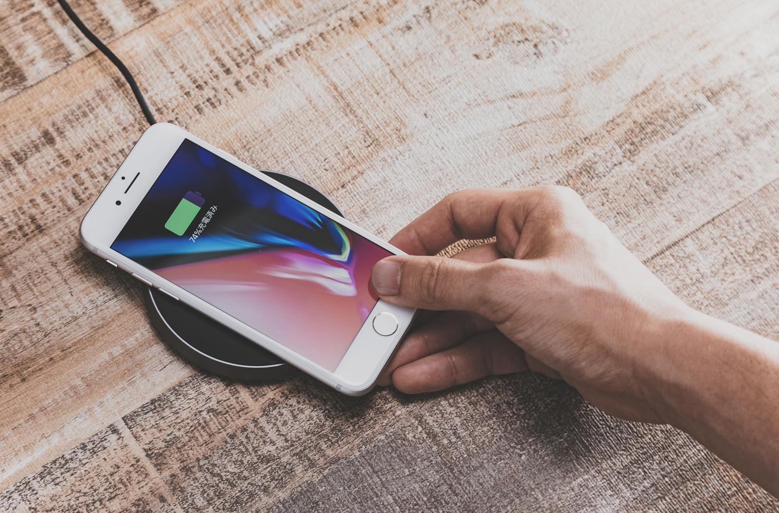「無線充電パッドにiPhoneをかざして充電する様子」の写真