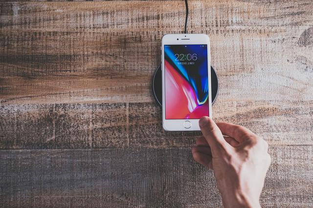 iPhone 8 をワイヤレス充電パッドにかざすの写真