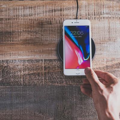 「iPhone 8 をワイヤレス充電パッドにかざす」の写真素材