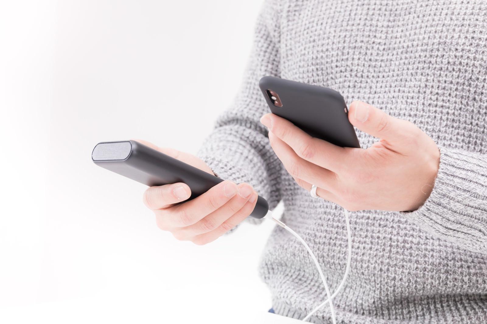 「モバイルバッテリーで充電しながらiPhoneを操作する男性の手元」の写真