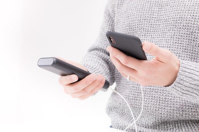 モバイルバッテリーで充電しながらiPhoneを操作する男性の手元の写真