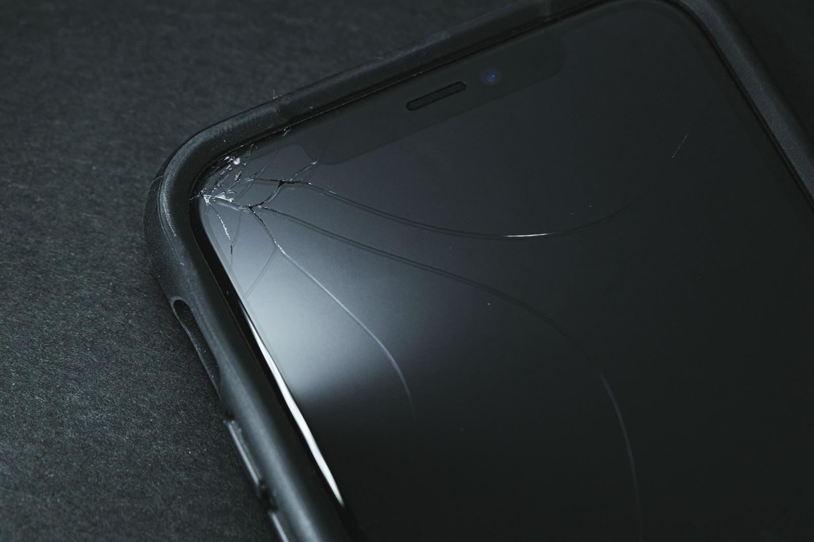 「保護ケースとヒビ割れしたiPhone」の写真