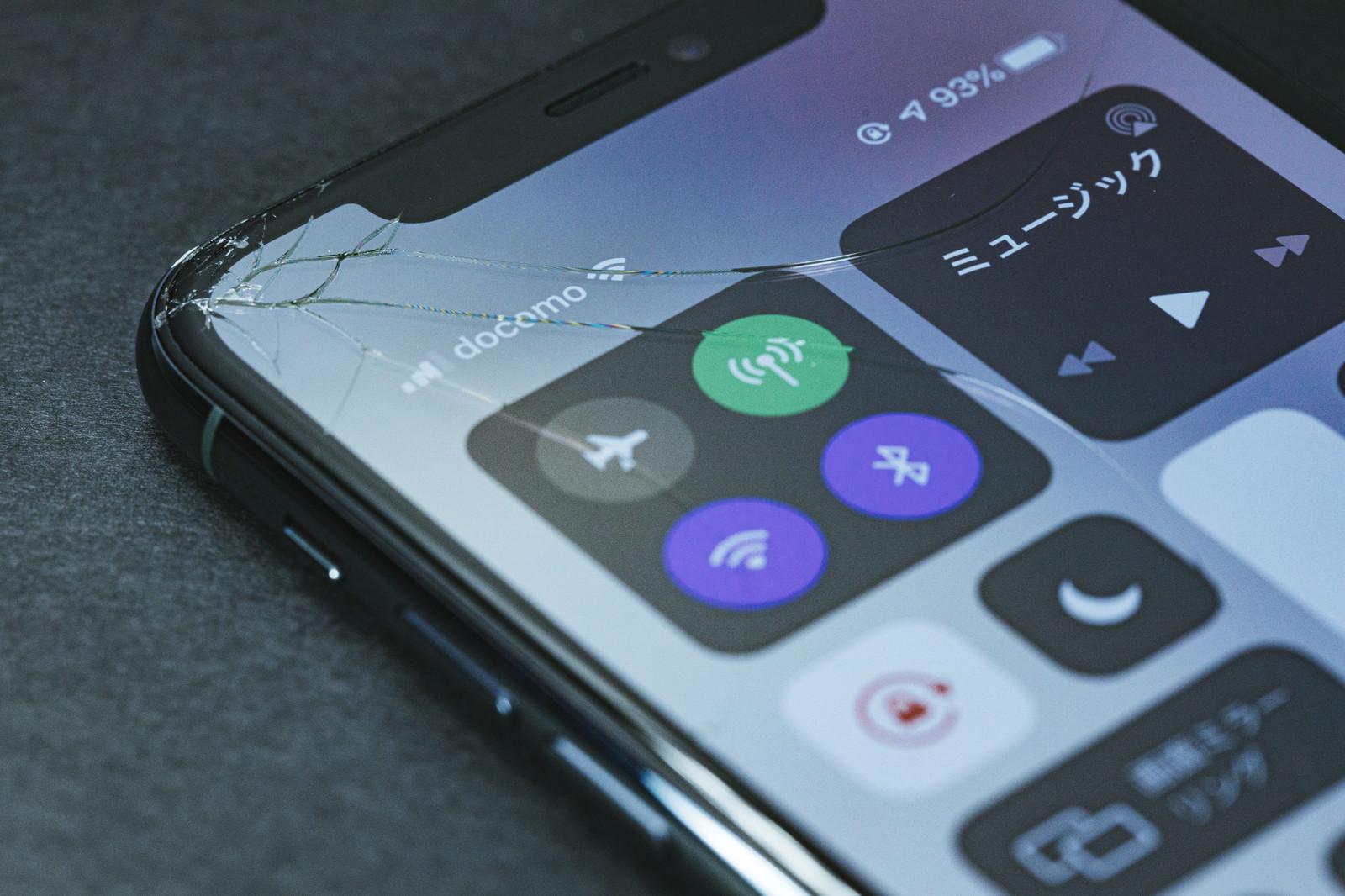 「画面割れした状態で起動したiPhone」の写真