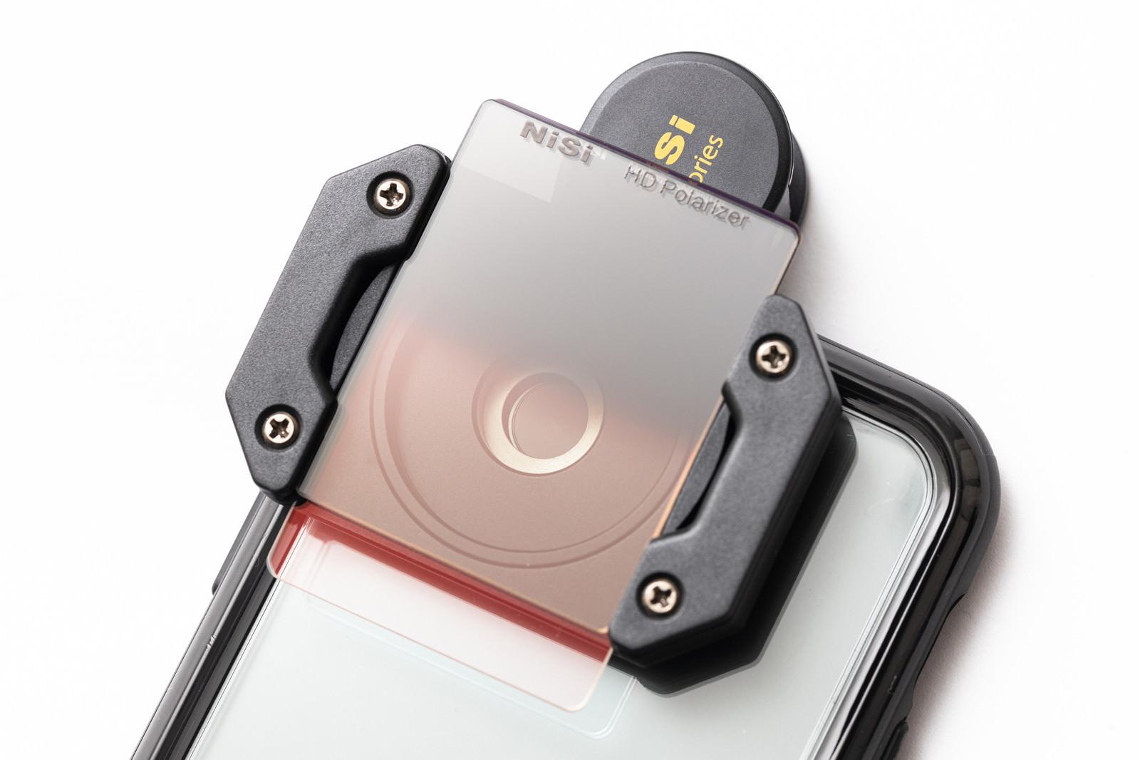 「iPhoneのカメラ部分に装着した角型フィルター」の写真