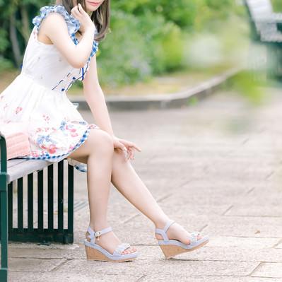 公園のベンチに座る彼女(首元を蚊に刺されてかゆい)の写真