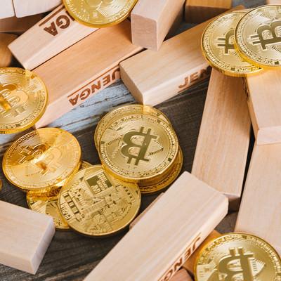 崩れたジェンガとビットコインの写真